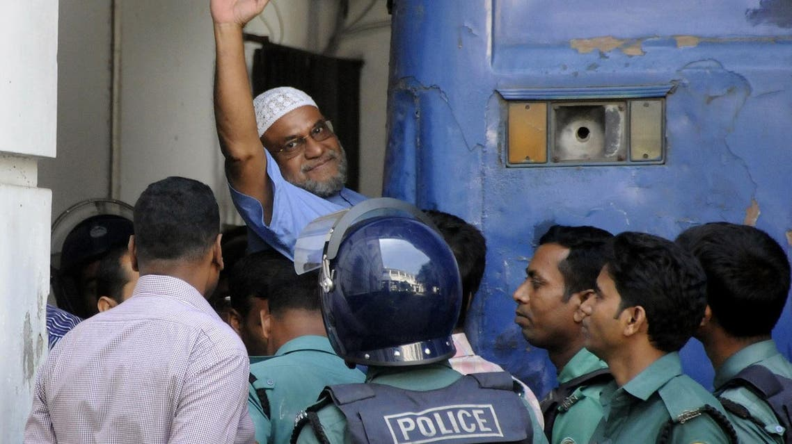Bangladeshi Jamaat-e-Islami party leader, Mir Quasem Ali waves as he enters a van at the International Crimes Tribunal court in Dhaka. (AFP)
