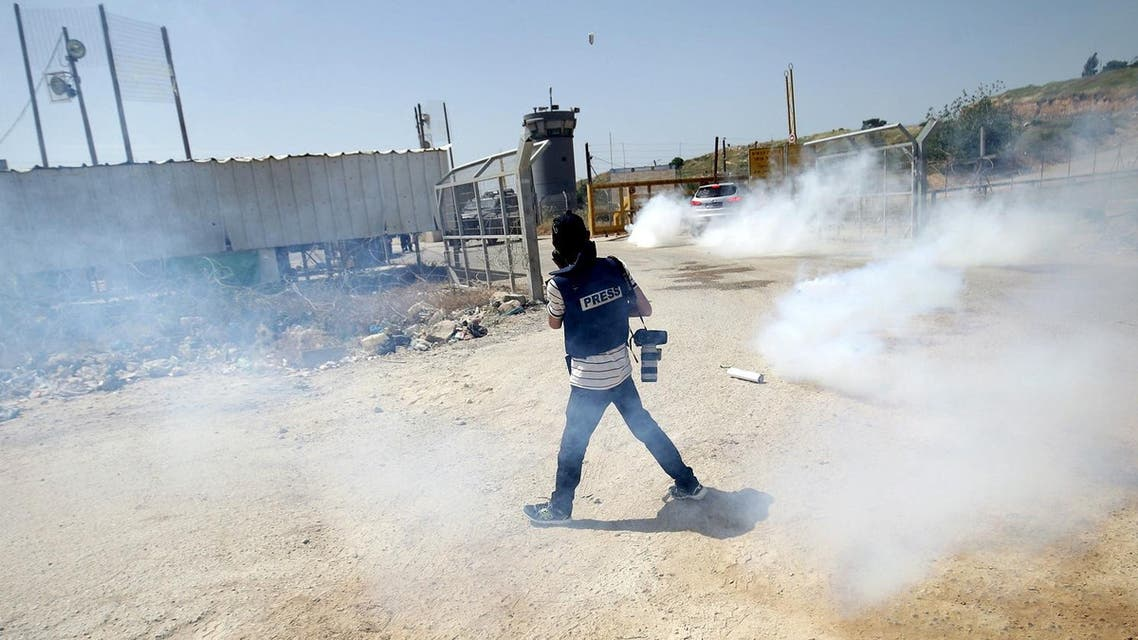 A photojournalist reacts to tear gas fired by Israeli troops during a protest calling for the release of Palestinian journalist Omar Nazal, who is held by Israel, near Israel's Ofer Prison near the West Bank city of Ramallah April 26, 2016. (Reuters)