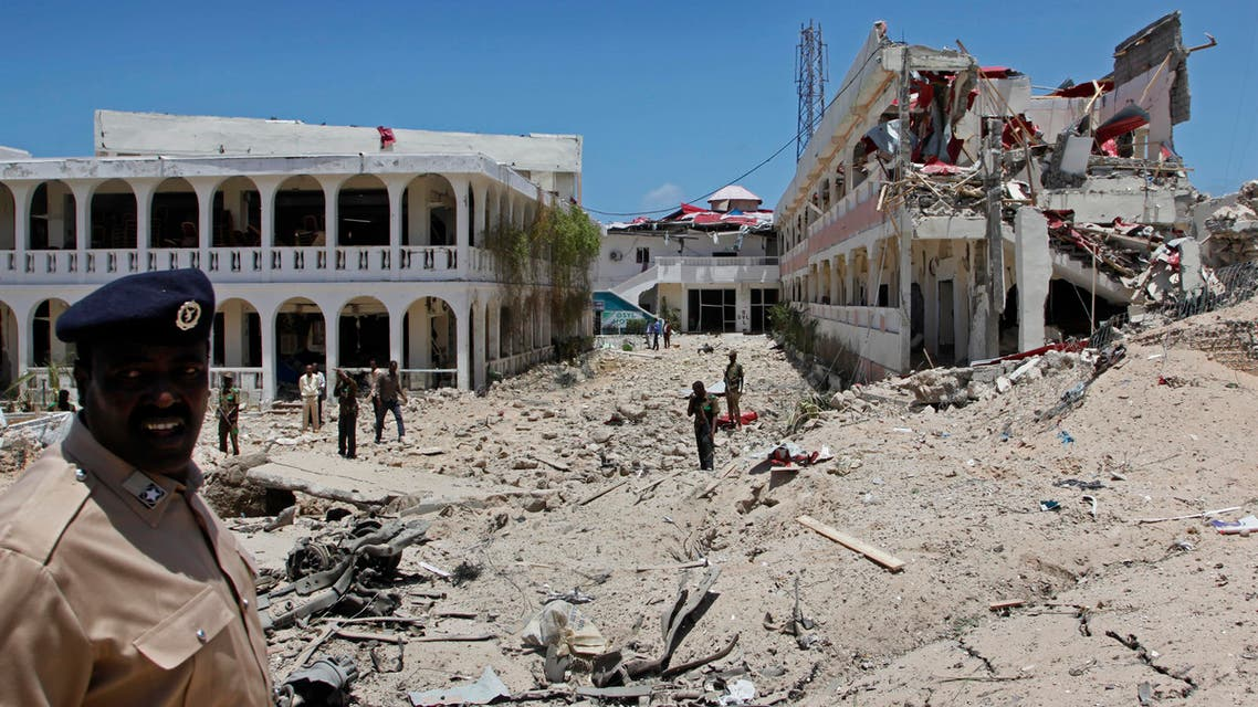 Somali soldiers stand near to a building destroyed by a blast near the presidential palace in the capital Mogadishu, Somalia Tuesday, Aug. 30, 2016. A suicide bomber has detonated an explosives-laden truck near the gate of Somalia's presidential palace in the capital on Tuesday, killing at least five people, police say. (AP Photo/Farah Abdi Warsameh)