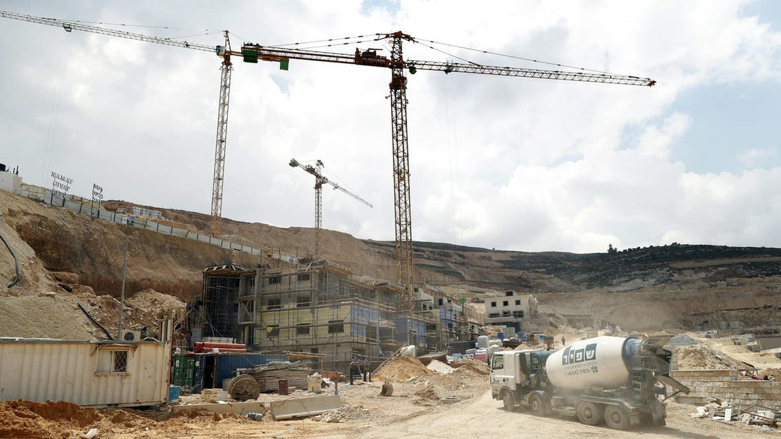 his file photo taken on April 14, 2016 shows workers and buldozers working at a construction site in the Israeli settlement of Givat Zeev near the West Bank city of Ramallah. AFP