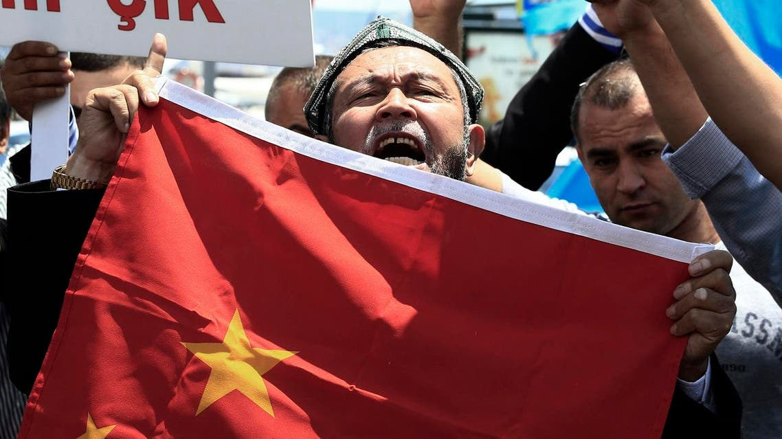 Uighurs living in Turkey and Turkish supporters, chant slogans as they hold a Chinese flag before burning it during a protest near China's consulate in Istanbul. (File photo: Reuters)