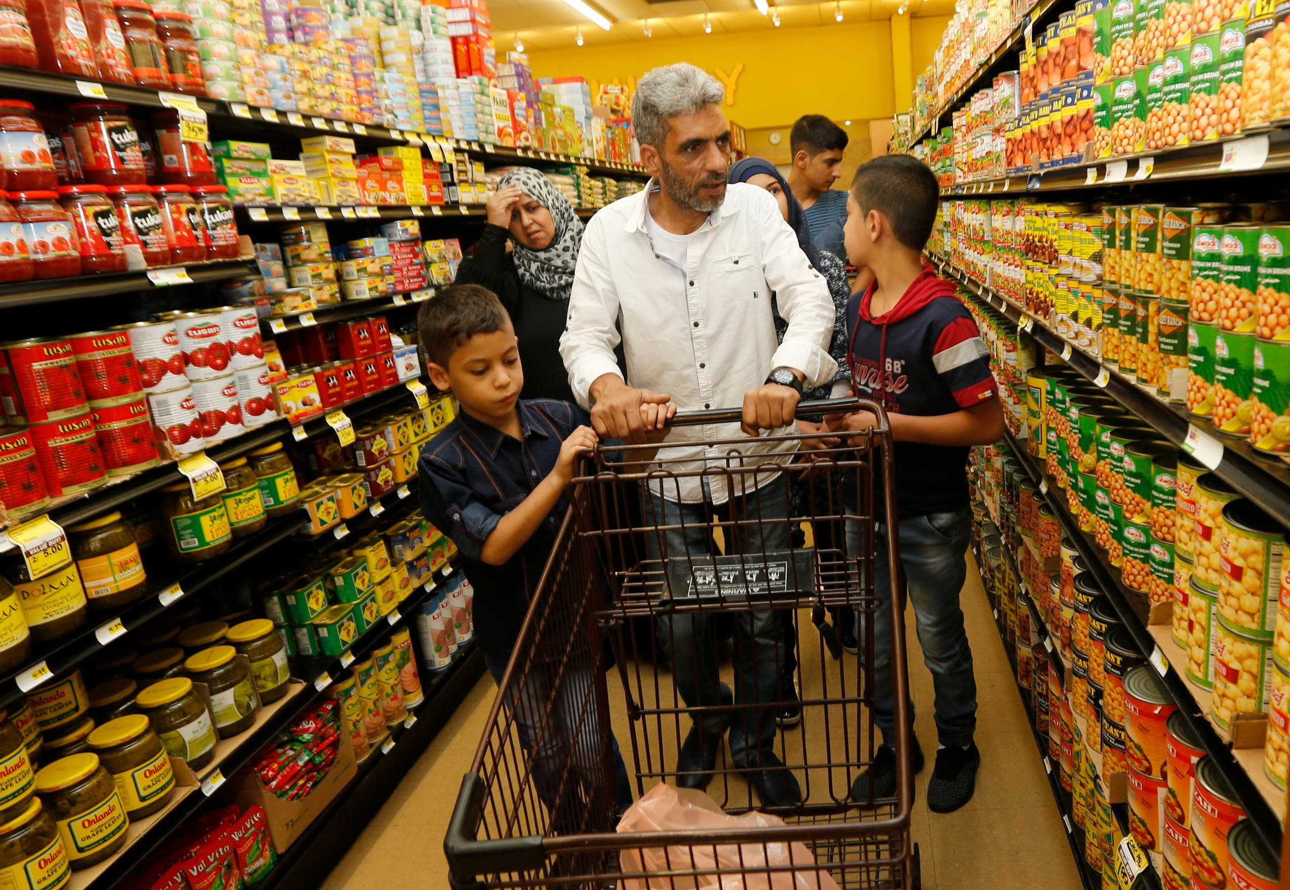 Nadim Fawzi Jouriyeh, a Syrian refugee who arrived in the United States this week with his family, pushes a shopping cart with sons, Farouq Nadim Jouriyeh, left, and Hamzeh Nadim Jouriyeh, Wednesday, Aug. 31, 2016, in El Cajon, Calif. Days after participating in a ceremony in Jordan to mark the United States hitting its target of taking in 10,000 Syrian refugees, the former construction worker and his family buy roasted chicken, milk and fruit for their new home outside San Diego. (AP Photo/Lenny Ignelzi)