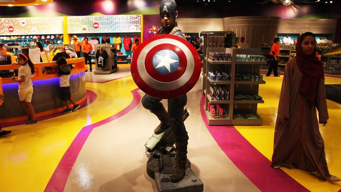 An Emirati woman walks past a statue of Captain America at the IMG Worlds of Adventure amusement park in Dubai, United Arab Emirates, on Wednesday, Aug. 31, 2016. The IMG Worlds of Adventure indoor theme park opened Wednesday in Dubai, hoping to draw thrill seekers to its air-conditioned confines. (AP Photo/Jon Gambrell)