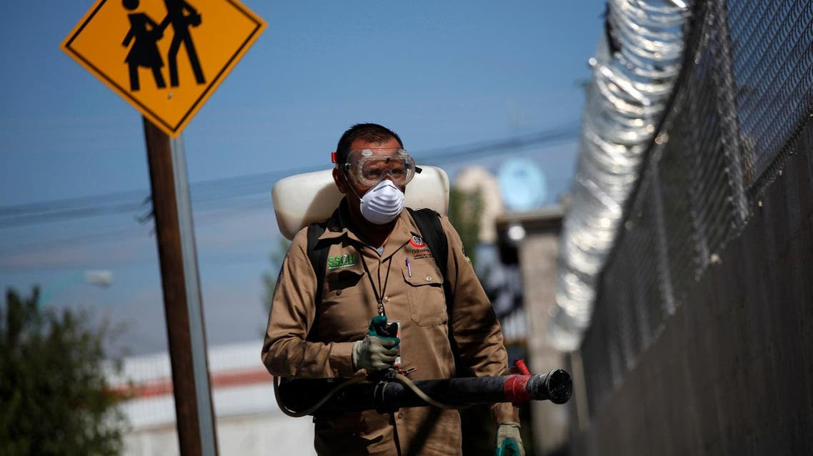 A municipal worker fumigates the perimeter of a school as part of the city's effort to prevent the spread of Chikungunya, Zika and West Nile virus. (Reuters)