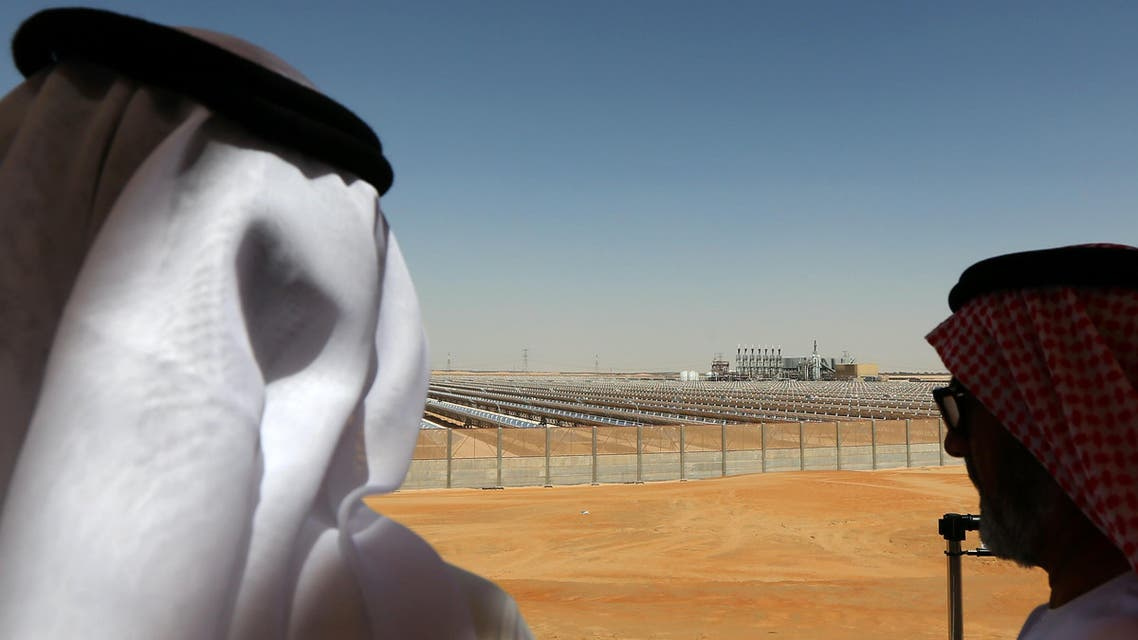 •Emarati men stand on a balcony overlooking the Shams 1, Concentrated Solar power (CSP) plant, in al-Gharibiyah district on the outskirts of Abu Dhabi (File Photo: AFP) af