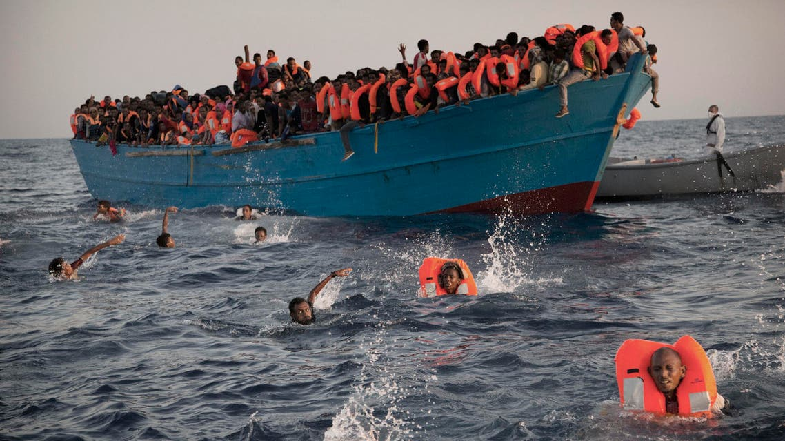 Migrants, most of them from Eritrea, jump into the water from a crowded wooden boat as they are helped by members of an NGO during a rescue operation at the Mediterranean sea, about 13 miles north of Sabratha, Libya, Monday, Aug. 29, 2016. (ap)