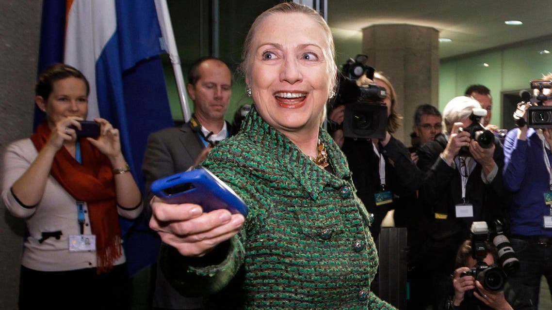 In this Dec. 8, 2011, file-pool photo, then-Secretary of State Hillary Rodham Clinton hands off her mobile phone after arriving for a meeting in The Hague, Netherlands. (AP)