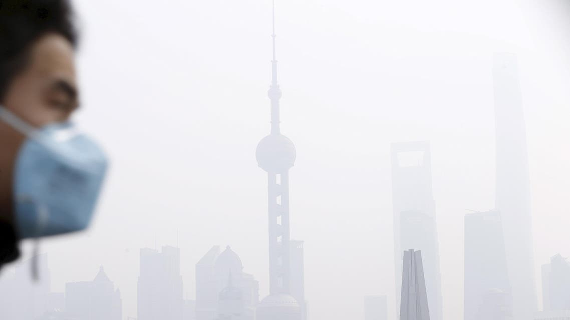 A man wearing a face mask walks on a bridge in front of the financial district of Pudong amid heavy smog in Shanghai, China, in this December 15, 2015 file photo. reuters