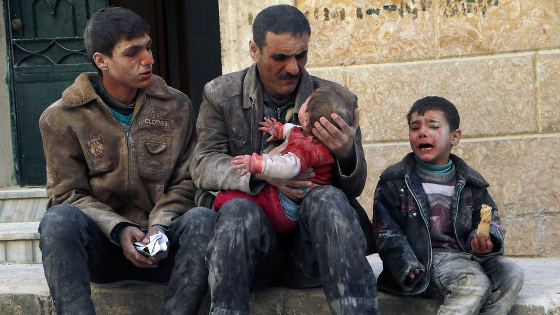 A man holds a baby saved from under rubble, who survived what activists say was an airstrike by forces loyal to Syrian President Bashar al-Assad in Masaken Hanano in Aleppo February 14, 2014. REUTERS