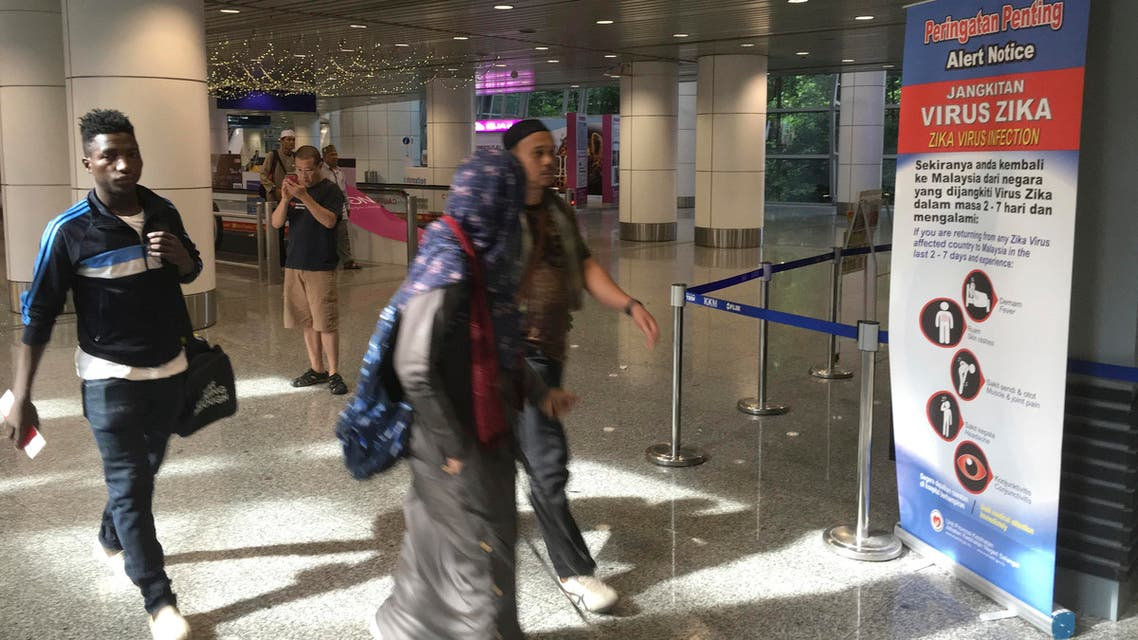 Travelers walk past a travel advisory on the Zika virus infection in Kuala Lumpur International Airport in Sepang, Malaysia, Sunday, Aug. 28, 2016. (AP)