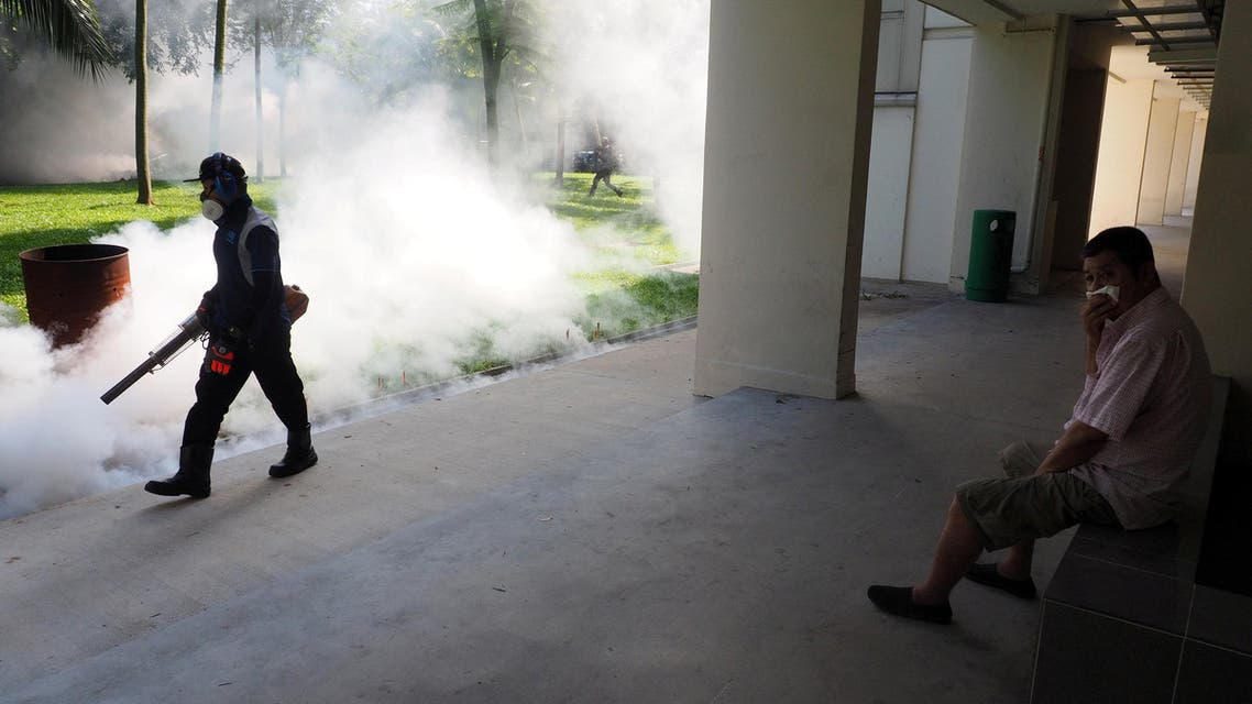 A resident shields his nose as pest control officer carry out fogging in the Aljunied Crescent cluster in Singapore, September 3, 2016 in this photo taken by Antara Foto. Antara Foto/MN Kanwa/via REUTERS