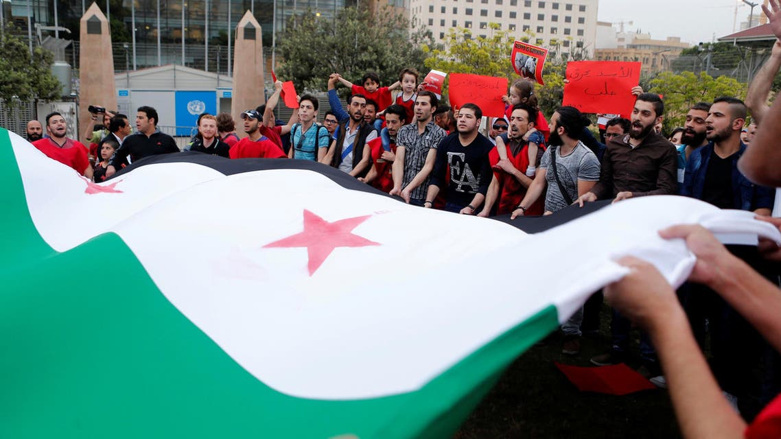 Protesters carry a giant Syrian opposition flag as they take part in a sit-in in solidarity with the people of Aleppo, in front of the offices of the U.N. headquarters in Beirut, Lebanon May 1, 2016. REUTERS