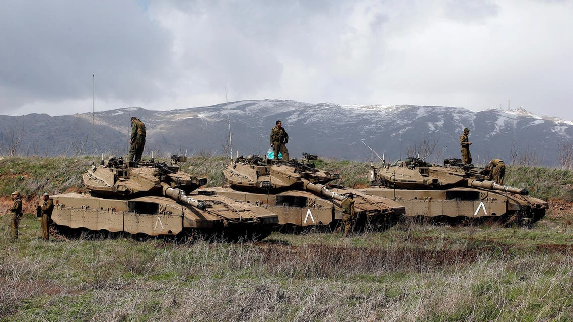 Israeli soldiers stand atop tanks in the Golan Heights near Israel's border with Syria March 19, 2014. REUTERS