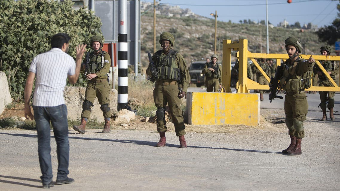 Israeli soldiers argue with a Palestinian at a checkpoint near the West Bank city of Nablus, Friday, June 10, 2016, after a Palestinian attempted a stabbing attack. Palestinian was shot and wounded, army said. (AP)