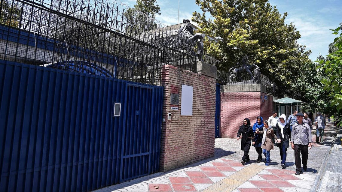 Iranian pedestrians walk past the main gate of British Embassy in Tehran, Iran, Saturday, Aug. 22, 2015. Iranian state-run media has reported the British Embassy in Tehran will reopen Sunday. The embassy has been closed for almost four years after hard-liners protesting the imposition of international sanctions over Iran's contested nuclear program stormed it in November 2011. (AP Photo/Ebrahim Noroozi)
