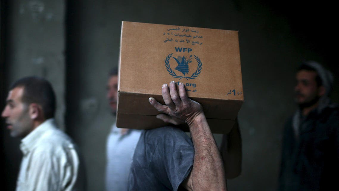 Men unloading aid boxes from a Red Crescent and United Nations(UN)aid convoy in the rebel held besieged town of Hamoria area, in the eastern suburbs of Damascus, Syria April 19, 2016. REUTERS