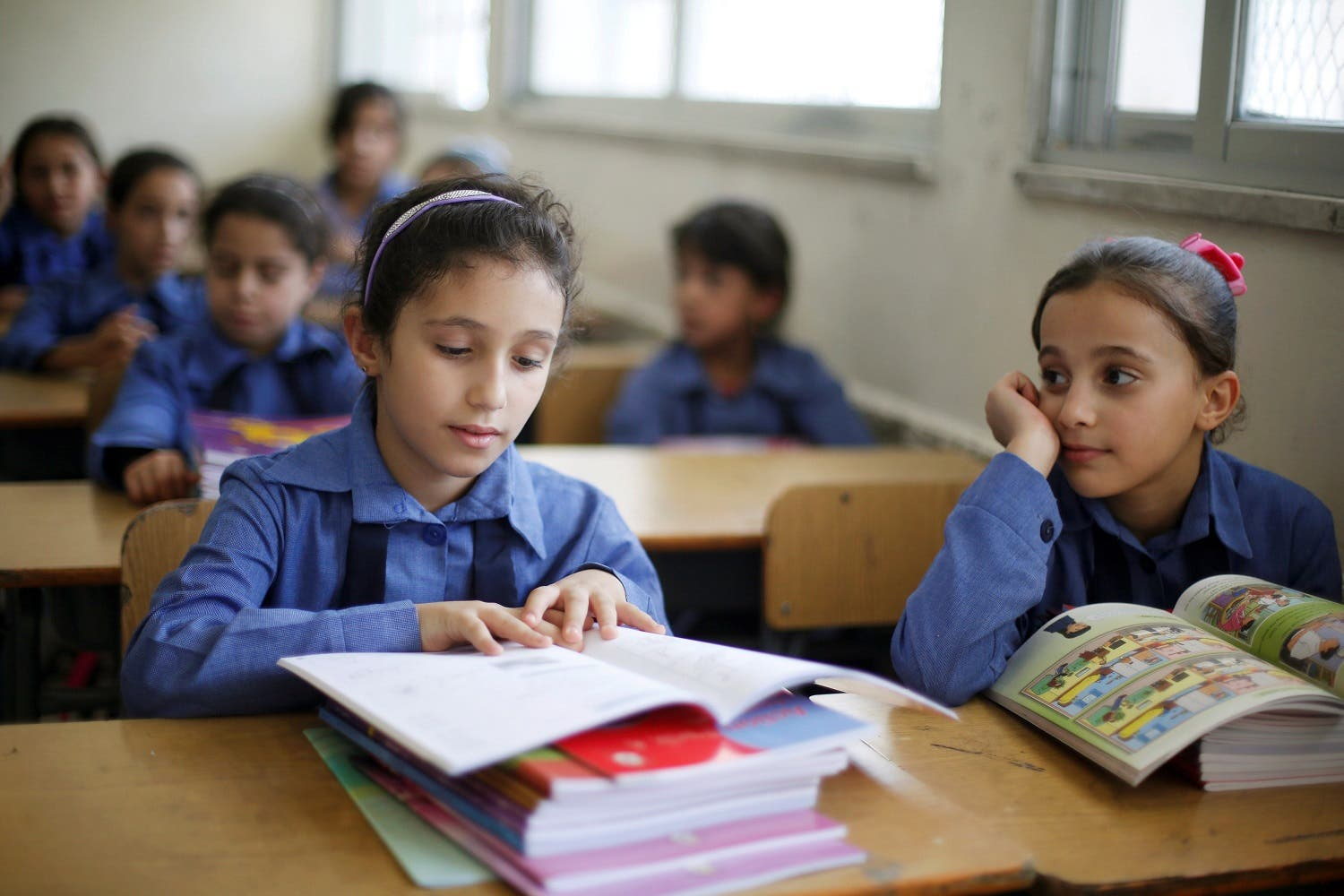 Refugee schoolchildren receive their new books on the first day of the new school year at one of the UNRWA schools at a Palestinian refugee camp al Wehdat in Amman. (Reuters)