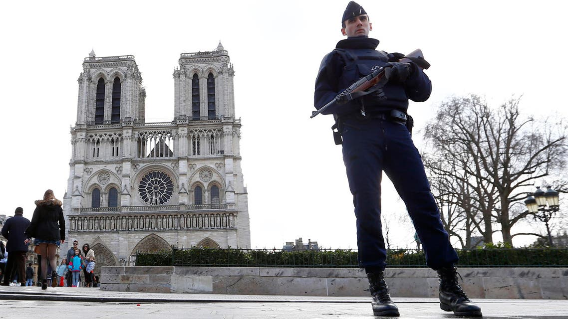 In this March 27, 2016 file photo, a French Police officer stands guards as worshipers arrive for the Easter mass at Notre Dame Cathedral, in Paris. (AP)