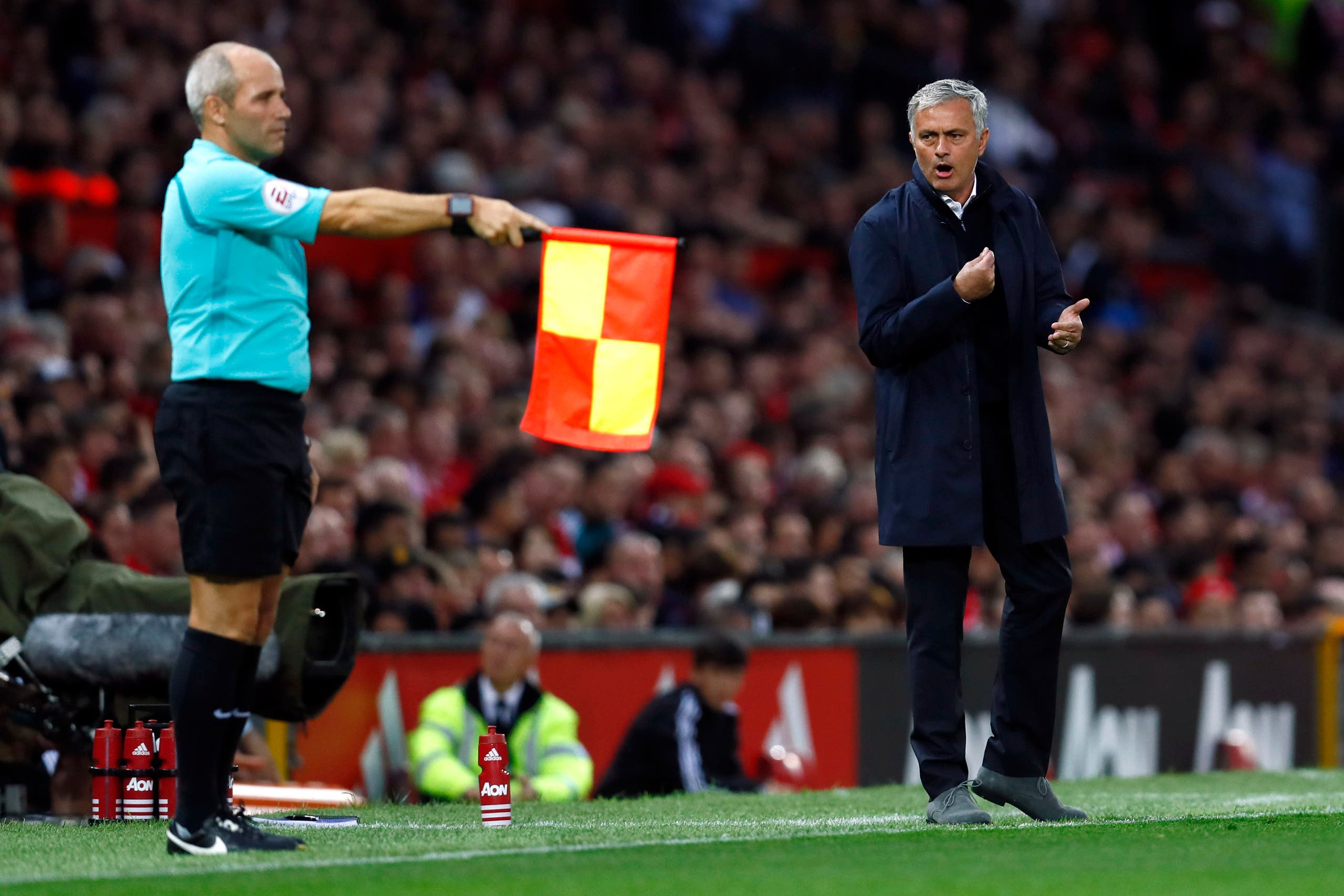 The linesman holds up his flag as Manchester United manager Jose Mourinho looks on. (Reuters)