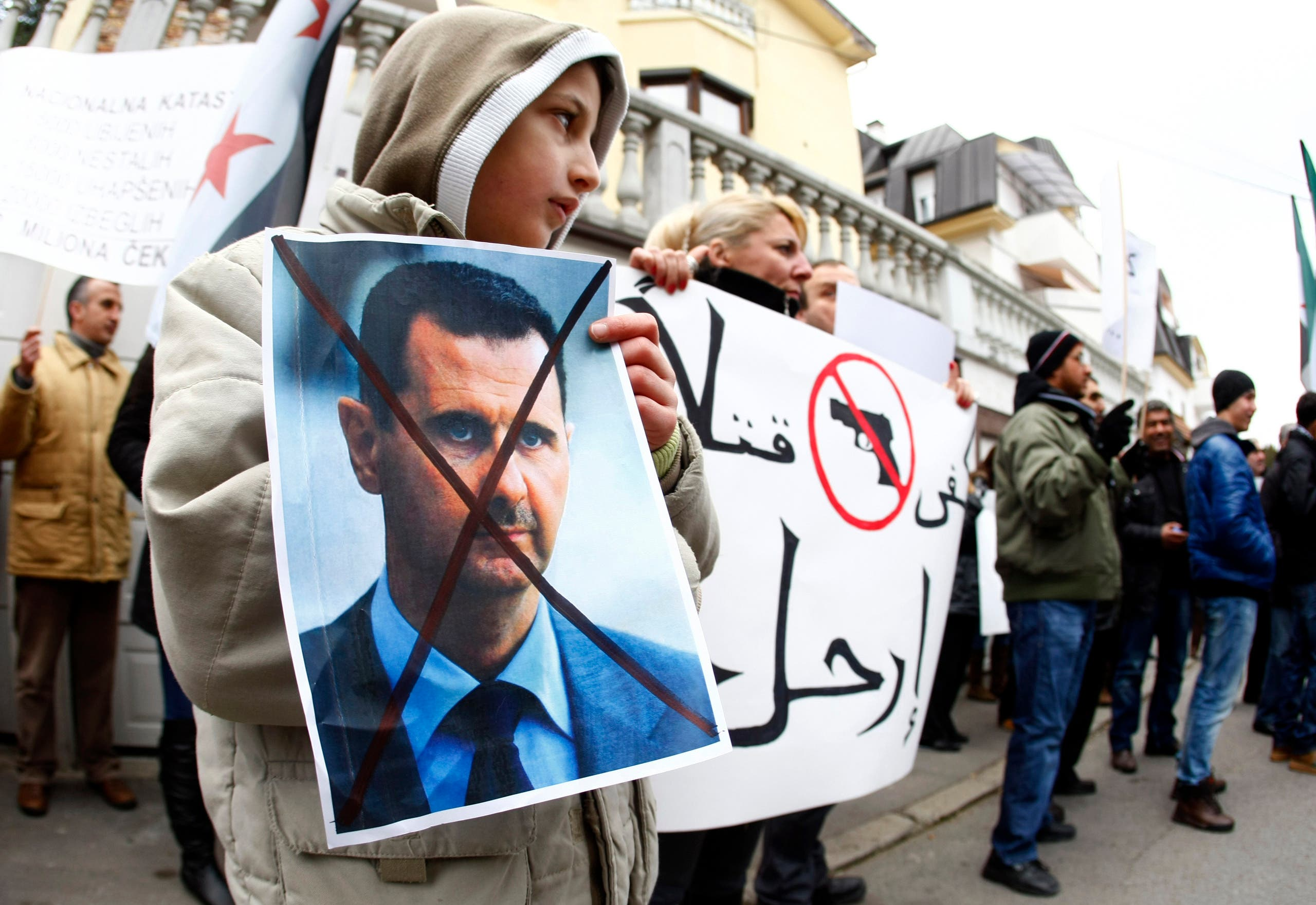 A Syrian immigrant holds a poster of Syrian President Bashar al-Assad during a protest against his regime in front of the Syrian embassy in Belgrade December 23, 2011. (File photo: Reuters)
