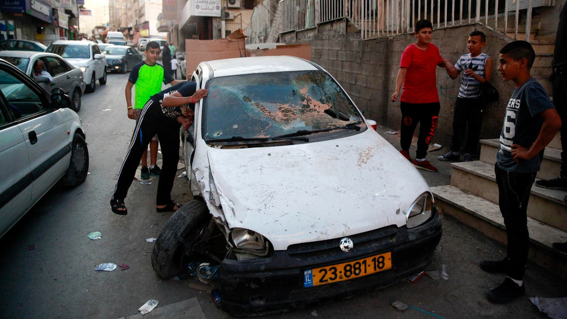 In this Monday Sept. 5, 2016 photo, Palestinian look at the car in which the driver was wounded and passenger killed by Israeli border police in Shuafat refugee camp in Jerusalem. ap