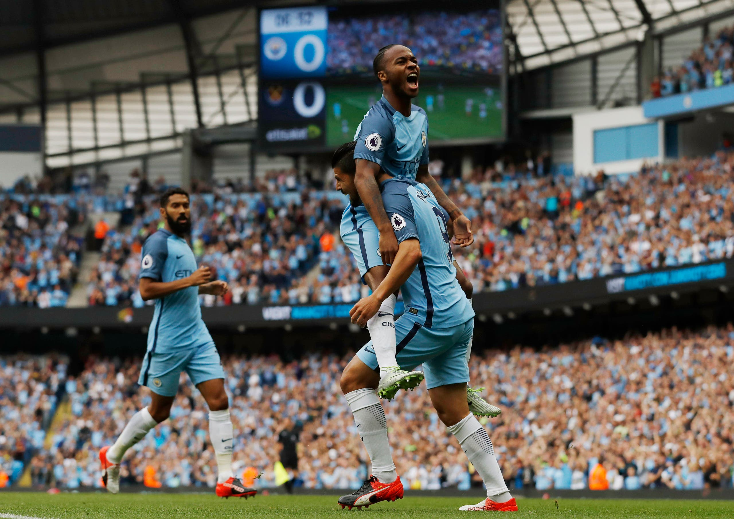 Manchester City's Raheem Sterling celebrates scoring their first goal with teammates. (Reuters)