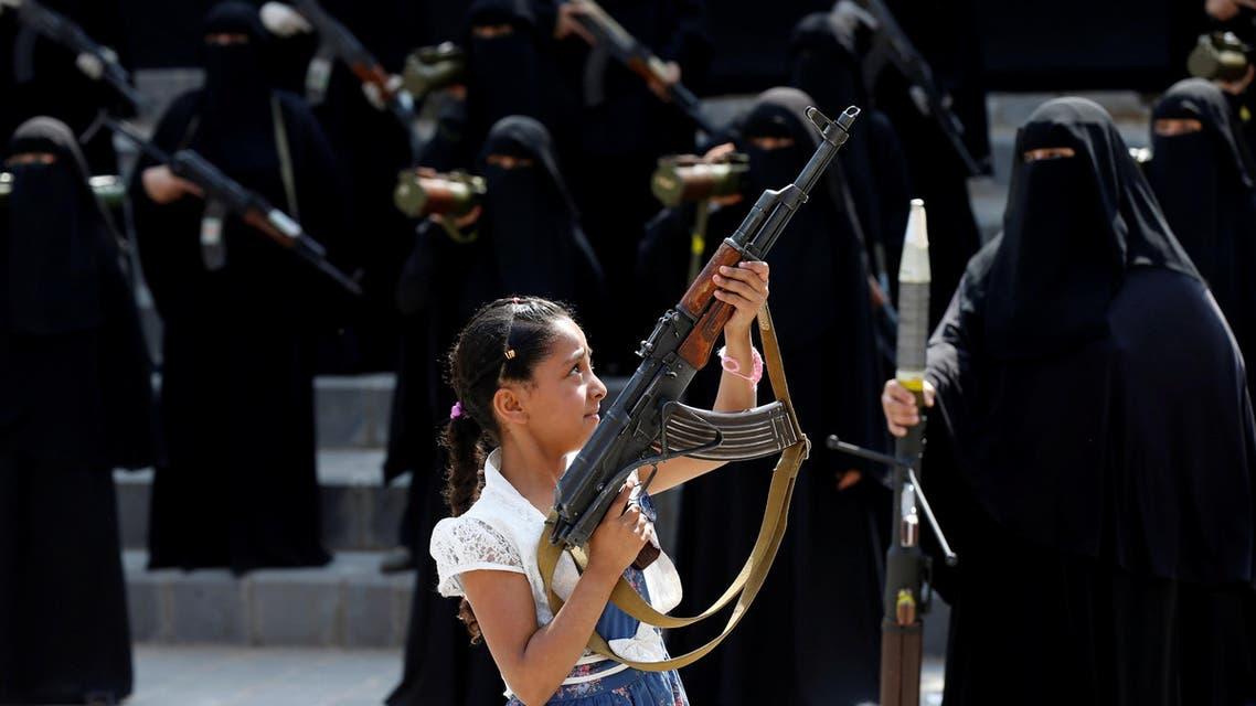 A girl holds a rifle in front of women loyal to the Houthi movement taking part in a parade to show support to the movement in Sanaa, Yemen September 6, 2016. reuters