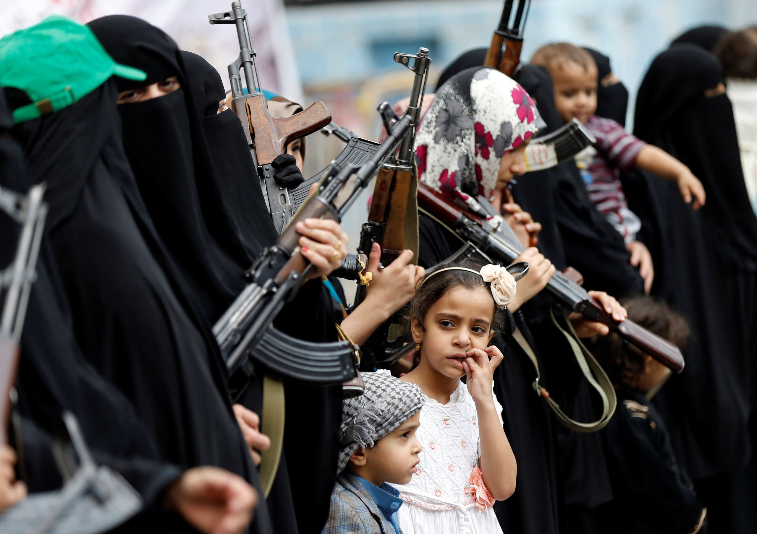 A girl looks at armed women loyal to the Houthi movement as they take part in a parade to show support for the movement in Sanaa, Yemen September 6, 2016. reuters