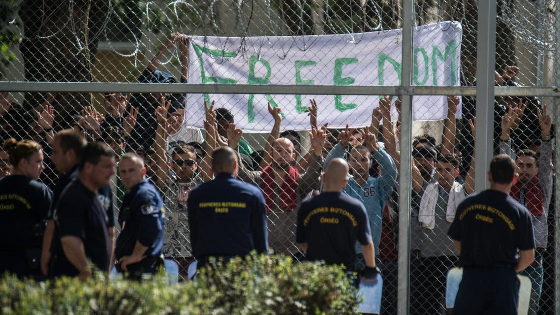 Migrants  protest demanding better conditions and faster administrative process deciding about their asylum claim as  security officers stand guard at a closed reception center in Kiskunhalas, Hungary. (AP)