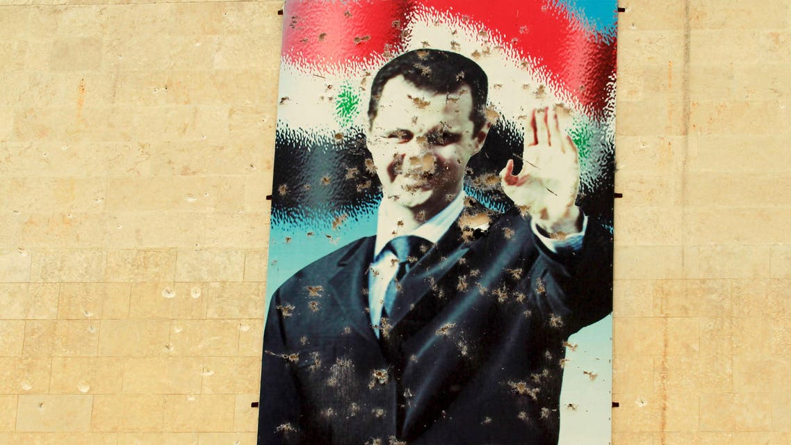 """A damaged picture of Syrian president Bashar Al-Assad is seen on a wall in Idlib city, after rebel fighters took control of the area March 28, 2015. The text on the poster reads in Arabic """"With Bashar"""". Picture taken March 28, 2015. REUTERS/Ammar Abdallah"""