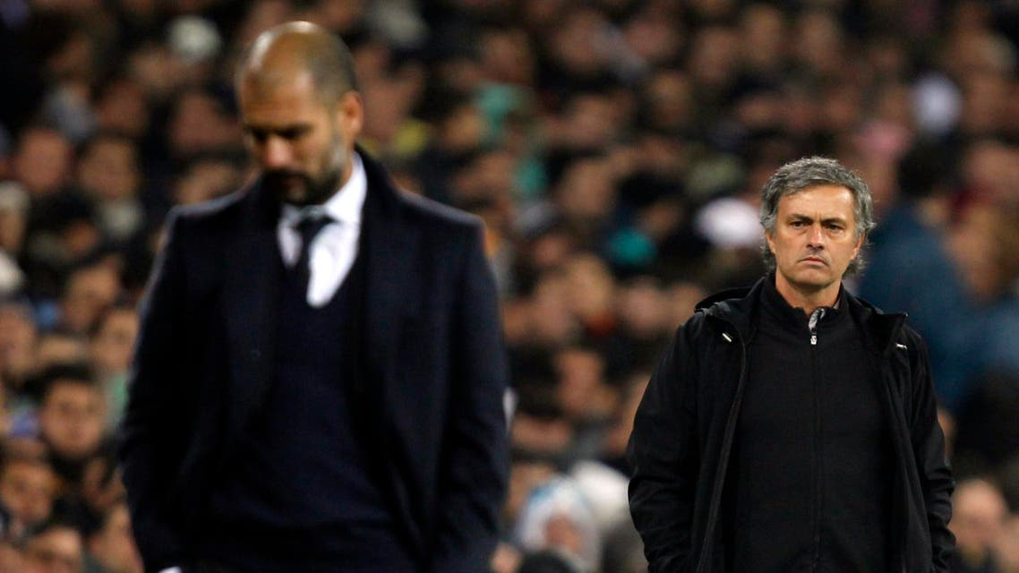 """Real Madrid's coach Jose Mourinho (R) looks at Barcelona coach Pep Guardiola after Xavi Hernandez goal during their Spanish first division soccer match, the """"Clasico"""", at the Santiago Bernabeu stadium in Madrid, December 10, 2011. REUTERS"""