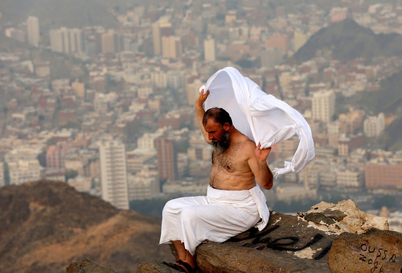 A Muslim pilgrim adjusts his ihram clothing on the top of Mount Al-Noor ahead of the annual Hajj pilgrimage. (Reuters)