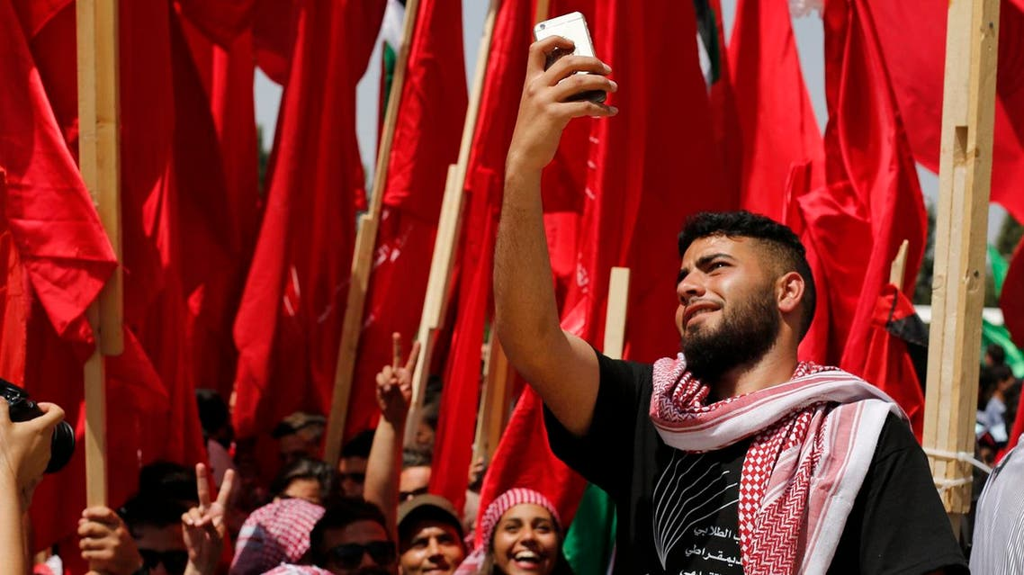 A Palestinian student supporting the Popular Front for the Liberation of Palestine (PFLP) movement takes a selfie during an election campaign rally for the student council at the Birzeit University. (AFP)