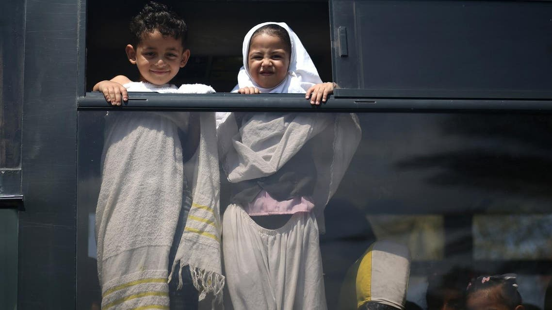 Palestinian children arrive by bus to take part in an exercise teaching them Hajj rituals during a school activity in Gaza City. (AFP)