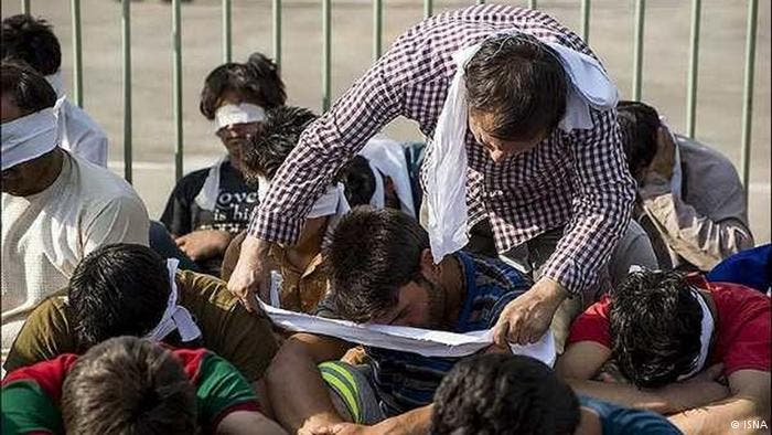 شرطي إيران يقوم بتعصيب أعين المعتقلين الأفغان