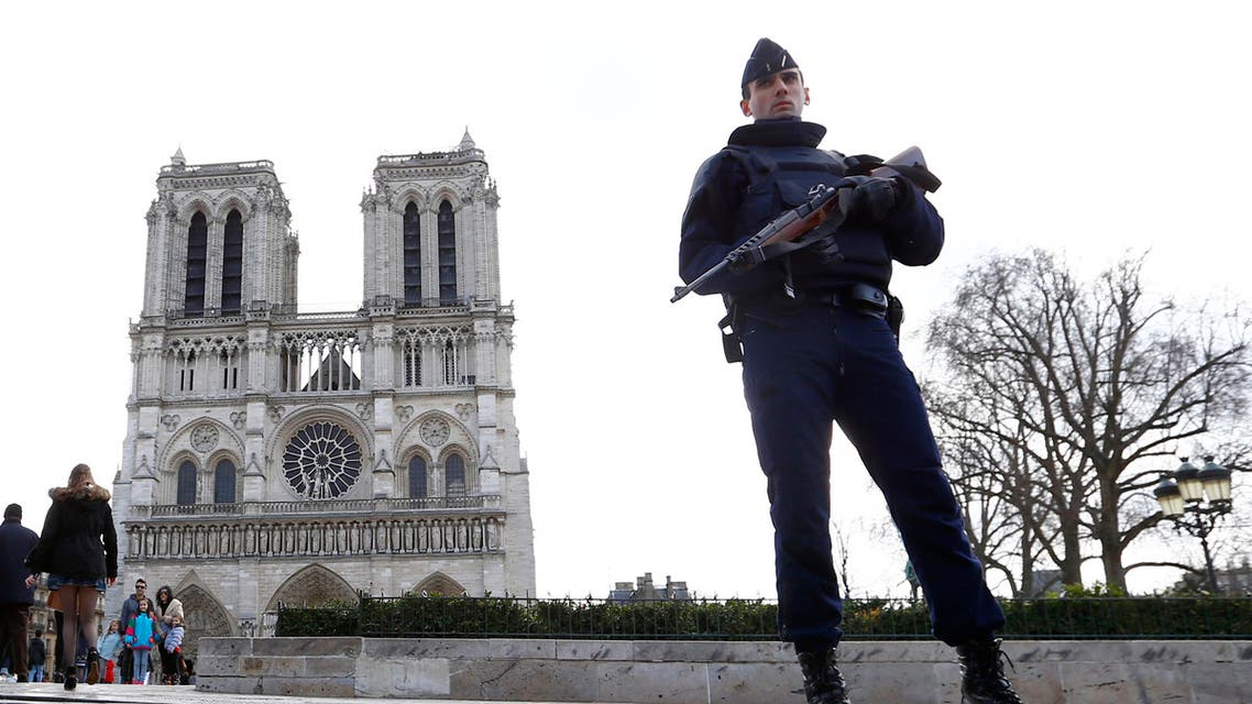 In this March 27, 2016 file photo, a French Police officer stands guards as worshipers arrive for the Easter mass at Notre Dame Cathedral, in Paris. Police officials say Wednesday Sept. 7, 2016 a terrorism investigation is under way into seven gas canisters found in a car parked near Notre Dame Cathedral in Paris. ap