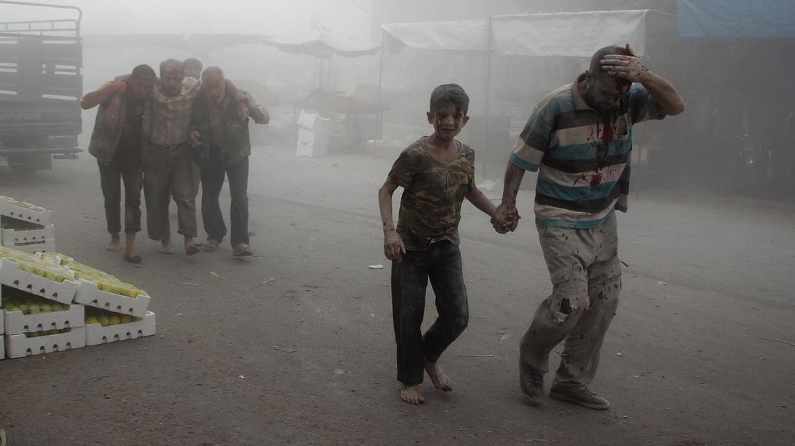 A wounded man and a child walk away as others help a victim at the scene of a reported air strike on the rebel-held northwestern city of Idlib on September 10, 2016. More than 290,000 people have been killed in Syria since its conflict erupted in March 2011, and millions displaced by the fighting. Omar haj kadour / AFP