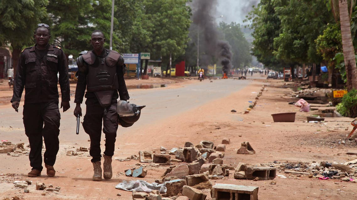 Mali police walk among the debris after a protest, in Bamako, Mali, Wednesday, Aug. 17, 2016. Protests in Mali's capital against the arrest of a popular activist radio host have turned violent, leaving at least three people dead and several injured. (AP)