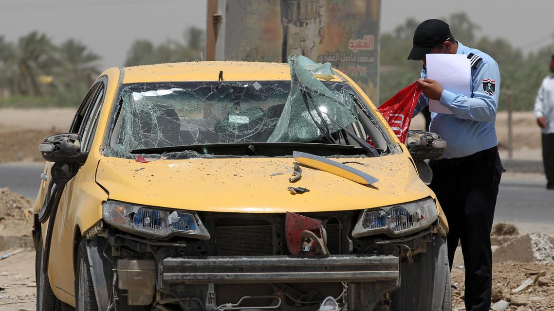 An Iraqi policeman looks at a damaged car as he inspects the site of a suicide bomb attack, claimed by the Islamic State group, at a checkpoint leading to the Husseiniyah area, northeast of the capital Baghdad on July 13, 2016. A suicide bomber detonated an explosives-rigged vehicle killing at least four people and wounding 21 people, the officials said. AFP