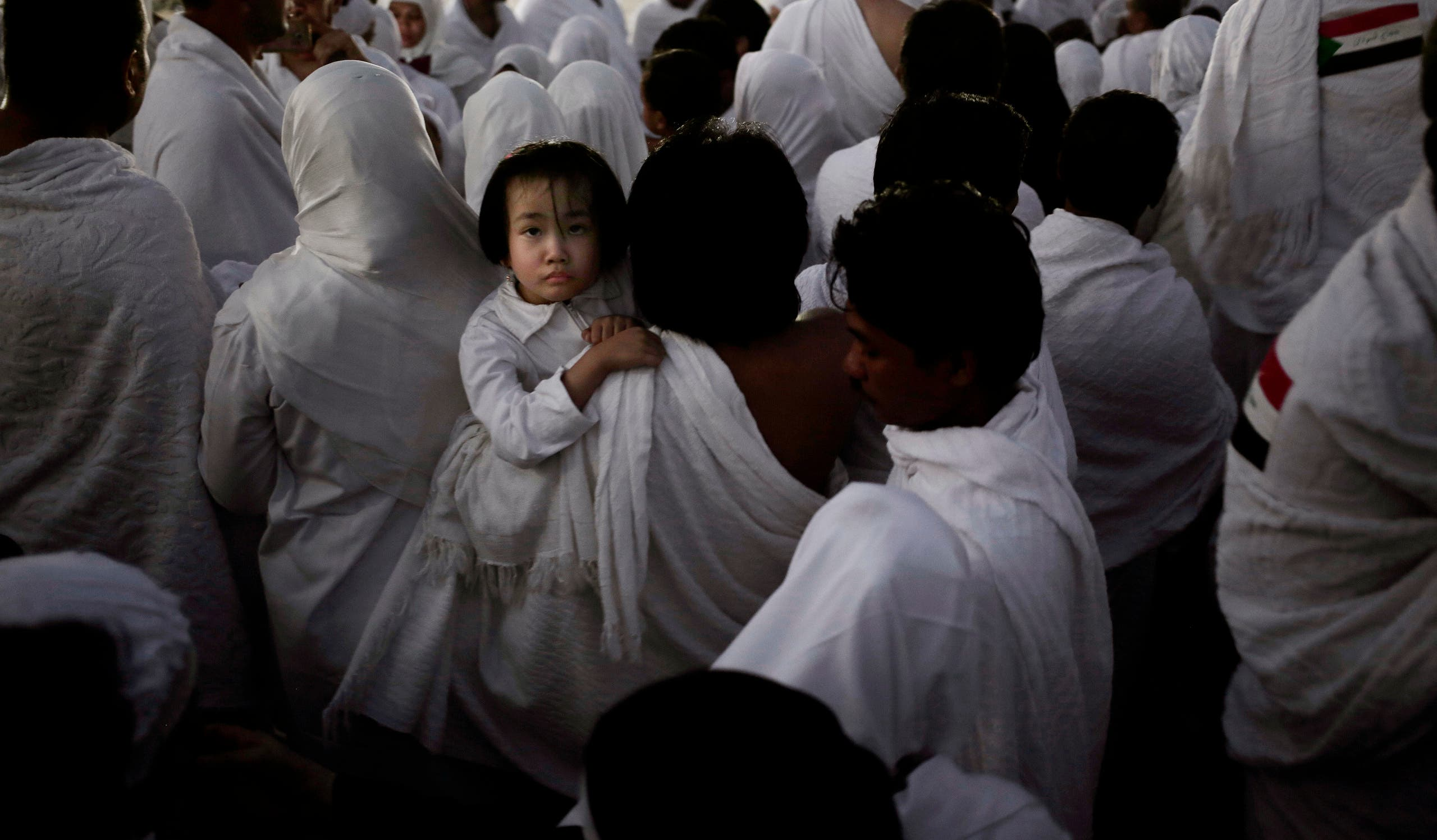An Indonesian father carries his daughter through the crowd after reaching the top of a rocky hill known as Mountain of Mercy, on the Plain of Arafat, during the annual hajj pilgrimage, ahead of sunrise near the holy city of Mecca, Saudi Arabia, Sunday, Sept. 11, 2016. Mount Arafat, marked by a white pillar, is where Islam's Prophet Muhammad is believed to have delivered his last sermon to tens of thousands of followers some 1,400 years ago, calling on Muslims to unite. (AP)
