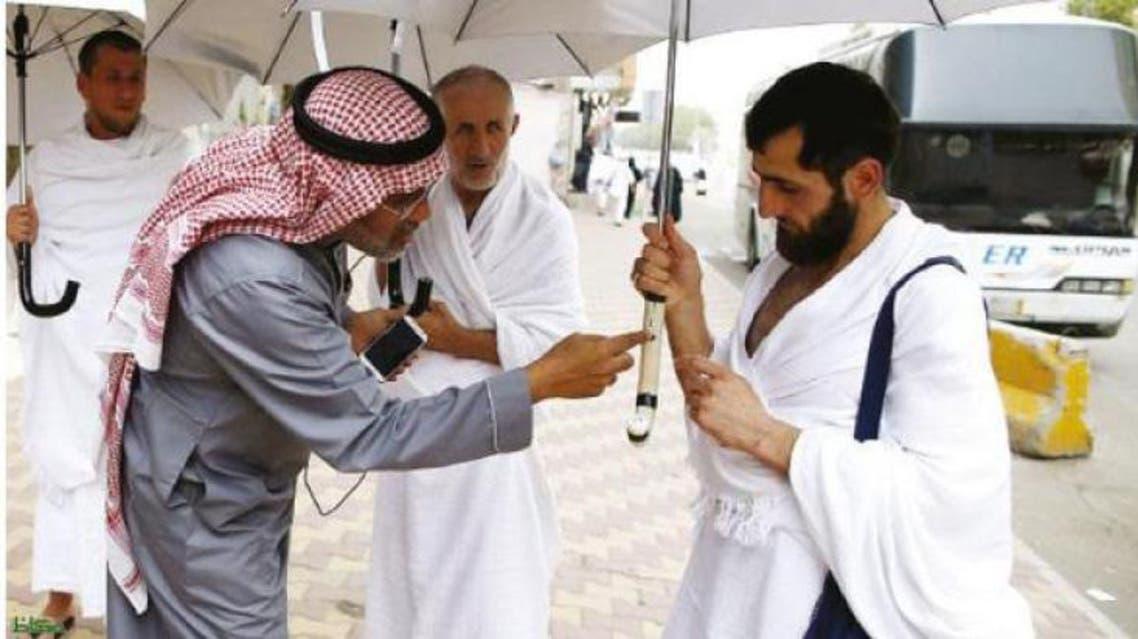 Kamal Badawi, a Saudi engineer from Makkah, explains salient features of a smart umbrella to a pilgrims. — Okaz