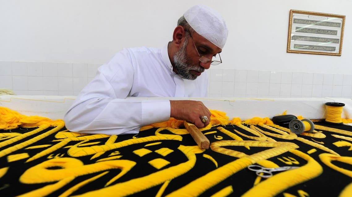 A Saudi worker sews Islamic calligraphy in gold thread on a drape to cover the Kaaba at the Kiswa factory in the holy city of Makkah. (AFP)