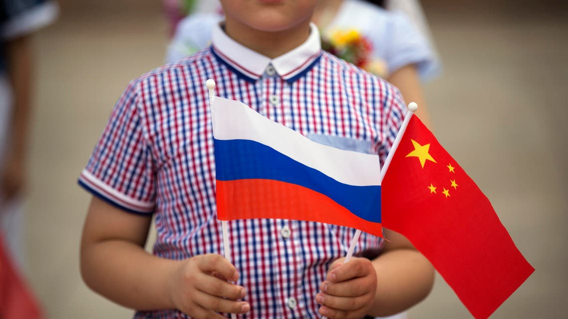 A boy holds Russian, left, and Chinese flags before a welcoming ceremony for Russian President Vladimir Putin at the Great Hall of the People in Beijing. (File Photo: AP)