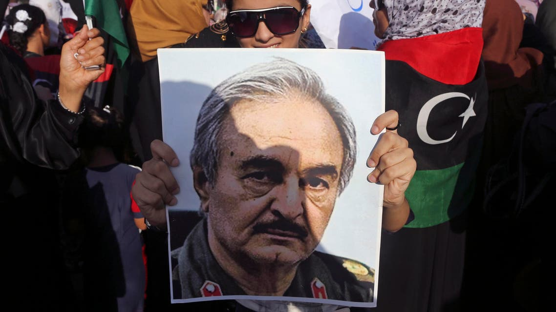 A woman holds a portrait of former Libyan army officer Khalifa Haftar, during a rally supporting Haftar, in Benghazi August 1, 2014. Two thousand people took to the streets of Benghazi on Friday to protest against Islamist militants and former rebel militias who have been fighting armed forces and taken over an important military base in the eastern Libyan city. The battle in Benghazi has pitted Islamist militants and militias against special forces who have joined ranks with a renegade former army officer, Khalifa Haftar, who had vowed to oust militants from the city. While Haftar initially gained support, critics dismiss him as a power-hungry, former Gaddafi ally. REUTERS/
