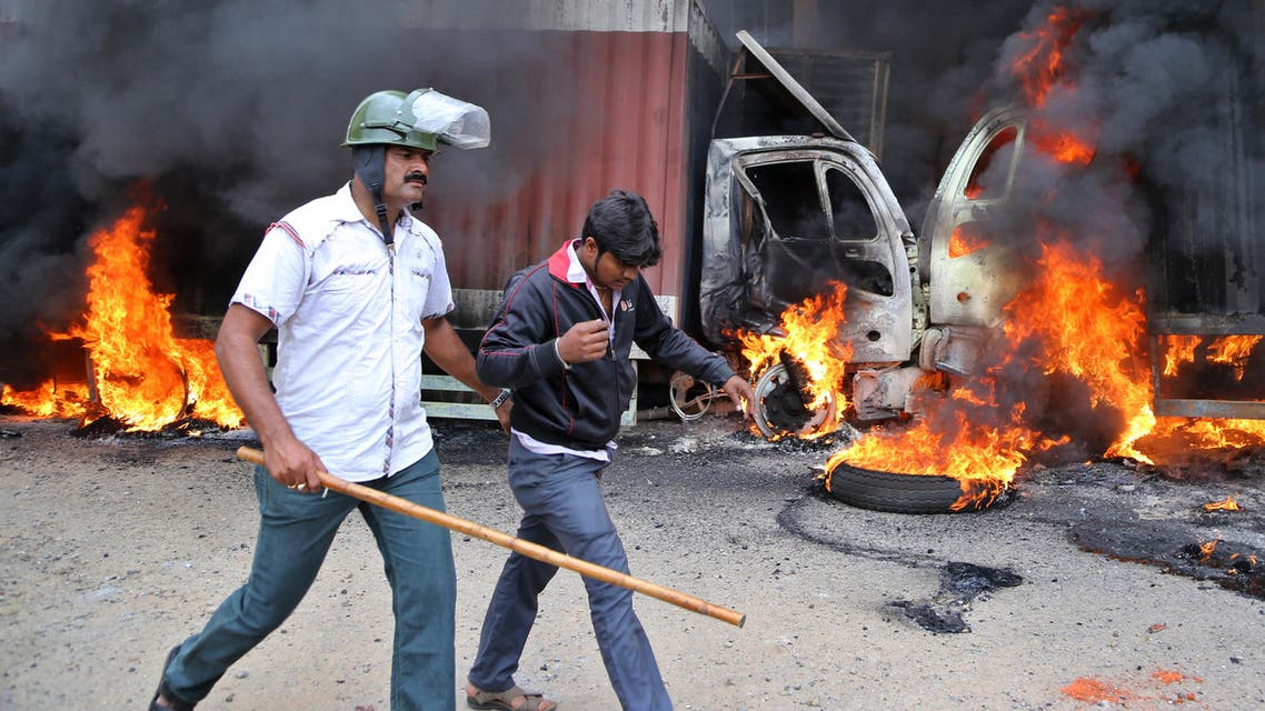 An Indian police officer detains a youth as they walk past burning trucks that belong to the neighboring Tamil Nadu state set ablaze by angry mobs in Bangalore, Karnataka state, India, Monday, Sept. 12, 2016. (AP)