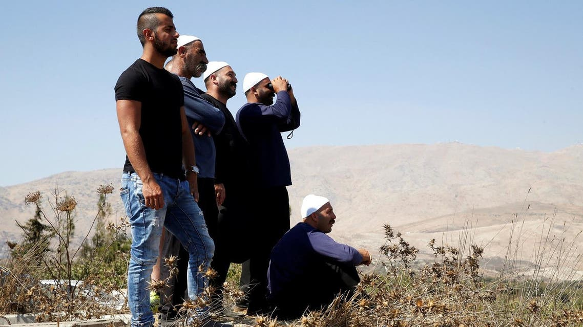 People watch fighting taking place in Syria as seen from the Israeli side of the border fence between Syria and the Israeli-occupied Golan Heights. (Reuters)