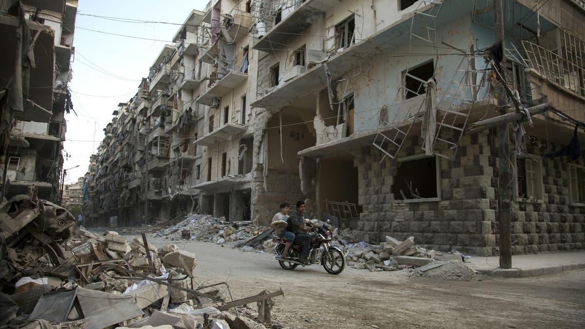 Syrian men ride a motorbike past damaged buildings in the rebel-held Bustan al-Qasr district in eastern Aleppo, on May 4, 2016.