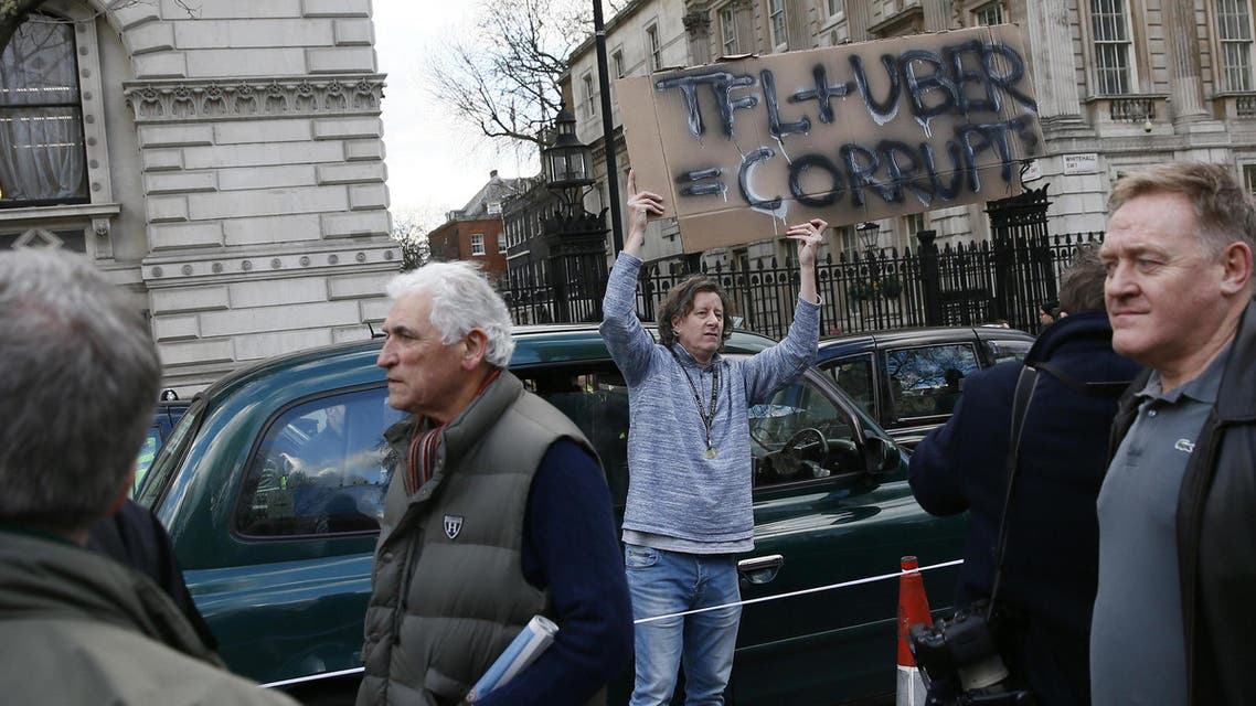 A London cab driver holds up a sign outside Downing Street during a protest against Uber on Whitehall in central London, Britain February 10, 2016. REUTERS/Stefan Wermuth/File Photo