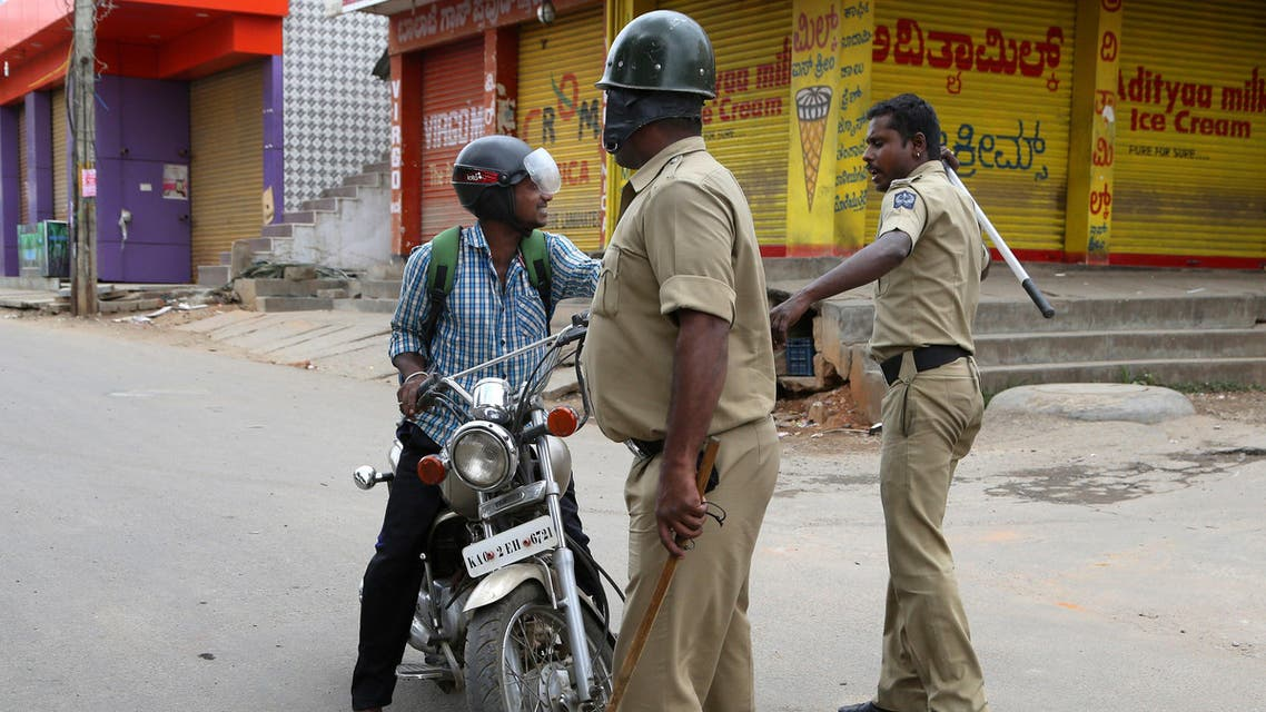 An Indian policeman hits a motorcyclist for defying curfew, a day after angry mobs burnt and vandalized buses from the neighboring Tamil Nadu state, in Bangalore, capital of the southern Indian state of Karnataka, Tuesday, Sept. 13, 2016. AP