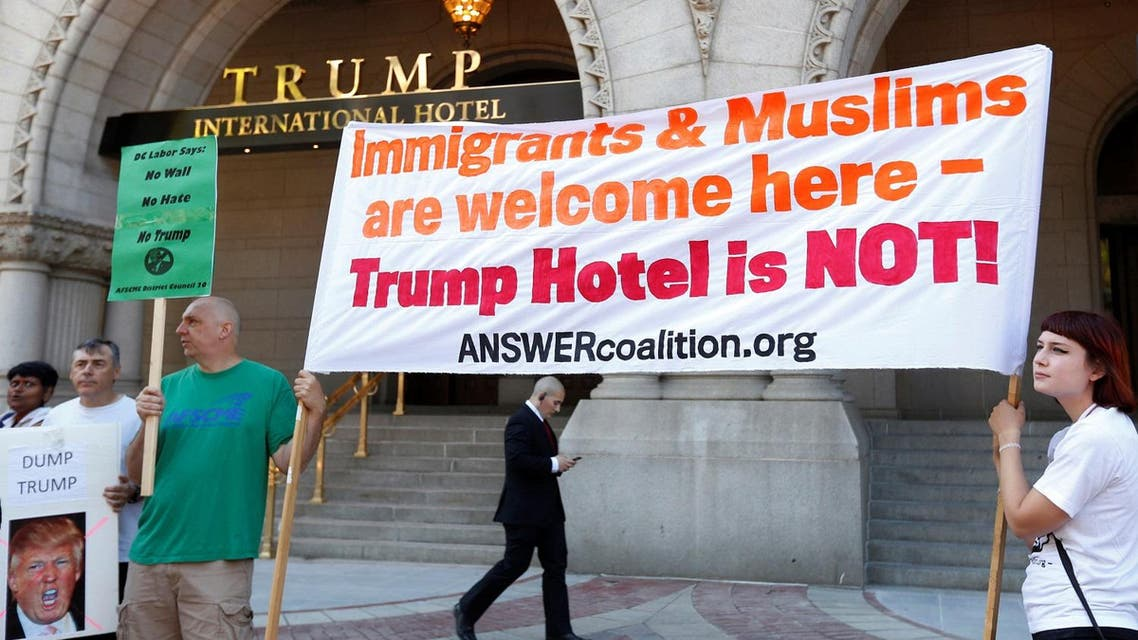 A security guard walks behind protesters holding signs outside the new Trump International Hotel on it's opening day in Washington. (Reuters)